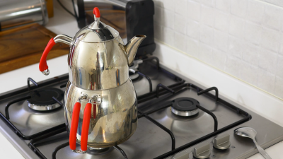 Traditional two tiered kettle with steam over a hot gas stove ...