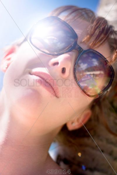 Stock Photo of Young woman in sunglasses resting her head on a ...